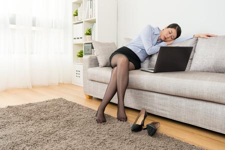 エレガントな美容女の子のオフィスワーカーは、彼女が仕事の後に眠っているときにソファに座って疲れを感じ、自宅の仕事に戻ってモバイルラッ 写真素材