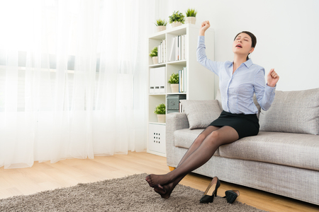 attractive elegant female company manager after work sitting on sofa couch stretching body to relax.
