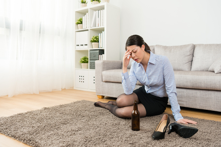 young attractive business woman losing work back to home sitting on floor drinking beer and getting drunk feeling headache painful.