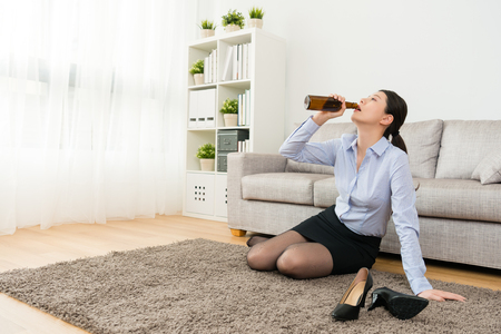 beautiful pretty female company manager losing important cooperation case feeling sadness and back to home sitting on floor drinking beer.