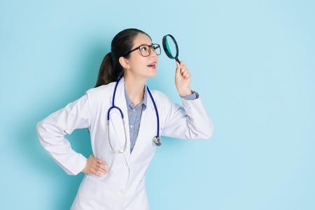 lächelndes tragendes Stethoskop Schönheitsmädchendoktors, das im blauen Hintergrund steht und das Vergrößerungsglaswerkzeug betrachtet oben das Suchen der medizinischen Informationen verwendet.