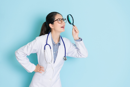 smiling beauty girl doctor carrying stethoscope standing in blue background and using magnifier tool looking at above searching medical information.