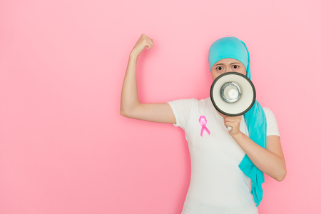 pretty confident female cancer patient face to camera using loudspeaker shouting and showing strength muscle isolated on pink background.