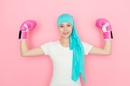 happy confident female cancer patient wearing boxing gloves standing in pink background and showing powerful muscle looking at camera.