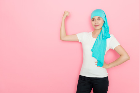 happy pretty cancer woman showing powerful strength muscle standing in pink wall background and looking at camera smiling.