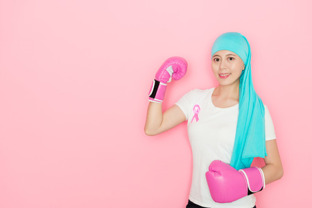 attractive young cancer patient woman wearing boxing gloves standing in pink background and looking at camera smiling showing powerful muscle. Stock Photo