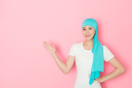 Confident pretty woman cancer patient making presenting posture standing in pink background. Stock fotó - 94586193