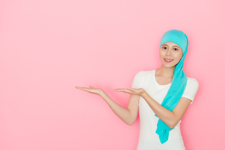 Confident young cancer patient woman standing in pink background and making presentation gesture showing empty area looking at camera smiling. Stock fotó - 94586194