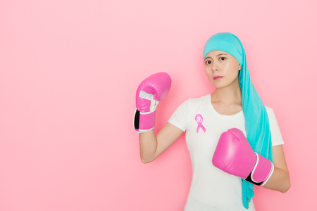 young pretty cancer girl with boxing gloves isolated on pink background.
