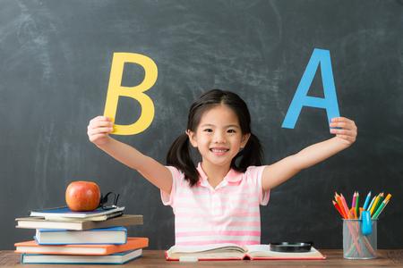 wesoła ładna studentka z powrotem do szkoły, studiując i siedząc w tle tablicy twarzą do kamery pokazując angielskie słowo.