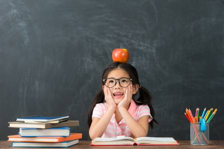 beautiful pretty female kid student studying in blackboard background and daydreaming prepare back to school.