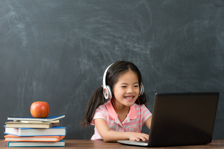 niños pequeños alegres de la niña que usan el ordenador portátil con los auriculares que estudian a través del sistema en línea del aprendizaje electrónico en fondo de la pizarra. Foto de archivo