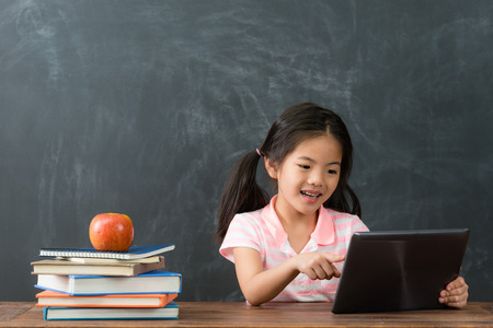 beautiful cute little girl student browsing online e-learning information with mobile pad computer and studying in blackboard background.