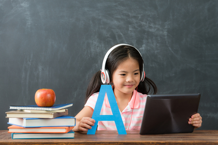smiling young female kid children using digital tablet pad watching online e-learning video to studying english in chalkboard background.