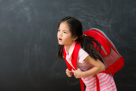 attractive cute little girl student back to school learning and carrying heavy bag feeling unhappy isolated on chalkboard background. Foto de archivo