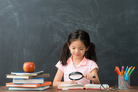attractive cute little girl using magnifier tool reading book in blackboard background and researching school homework to study.
