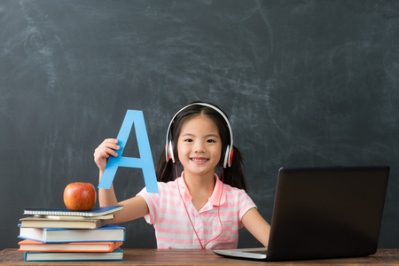 lovely beauty girl student using online e-learning studying in blackboard background and face to camera showing english word.