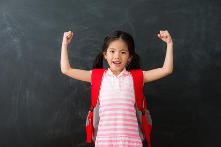 若い美しい小さな女の子の学生は、学校の勉強に戻って準備ができて宿題を終え、黒板の背景に立って、カメラのお祝いを見て腕を上げました。