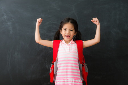 young beautiful little girl student successful finished homework ready back to school studying and standing in blackboard background raised arms looking at camera celebration.