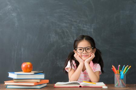 Preciosa niña bonita niña de regreso a la escuela sentado en clase estudiando y cara a cámara sonriendo sobre fondo de pizarra. Foto de archivo