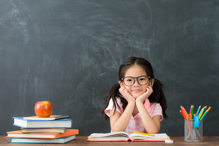 lovely pretty little kid girl back to school sitting in class studying and face to camera smiling on blackboard background.