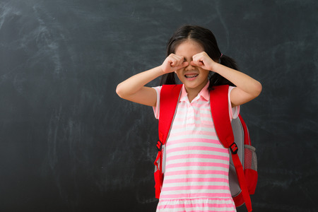 pretty young female kid children dislike studying standing in chalkboard background crying when she need back to school learning.