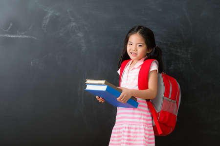 unhappy cute little girl student holding heavy textbook face to camera showing suffering emotional and standing in blackboard background prepared back to school studying.