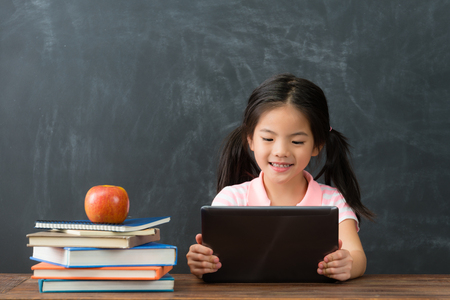 pretty young female kid children using mobile digital tablet studying in chalkboard background.