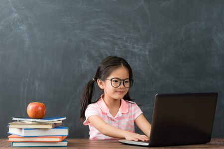 attractive beauty girl children using laptop computer doing homework studying in chalkboard background. back to school concept.