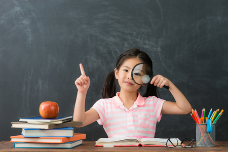 beautiful young female kid student showing magnifier looking at camera and having good idea pointing air in chalkboard background.