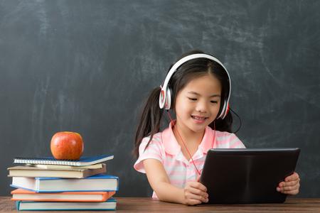 Estudante bonito feliz da menina pequena que senta-se no fundo do quadro-negro e que usa o computador móvel da almofada que estuda através do sistema em linha do ensino eletrónico. Foto de archivo - 94625577