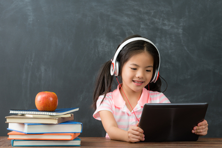 happy beautiful little girl student sitting in blackboard background and using mobile pad computer studying through online e-learning system. Standard-Bild