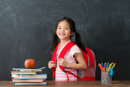 happy cheerful female kid children carrying studying bag ready back to school learning and looking at camera smiling in blackboard background.