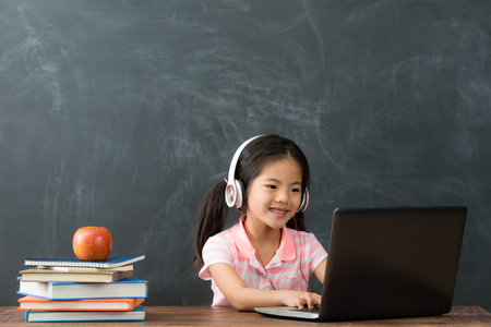 happy beautiful female student sitting in blackboard background and using mobile computer studying through online e-learning system.