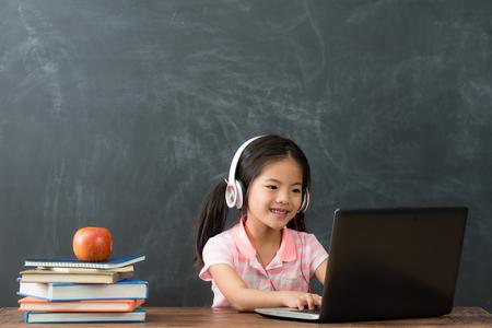 feliz estudiante hermosa que se sienta en el fondo de la pizarra y que usa la computadora móvil que estudia a través del sistema en línea del aprendizaje electrónico.