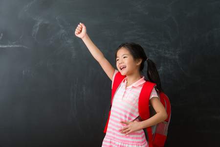 pretty lovely female kid children prepared back to school isolated on chalkboard background.