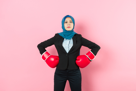 confident professional muslim business woman manager wearing boxing gloves face to camera and hands put on waist standing in pink background. Stock Photo