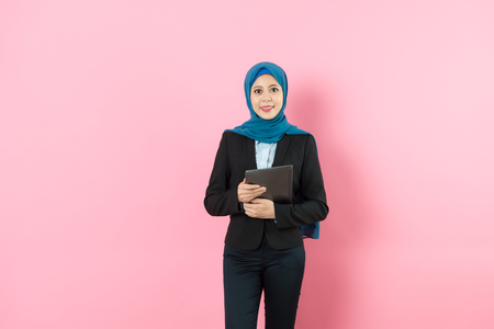 professional happy muslim business woman holding mobile pad computer face to camera isolated on pink background.