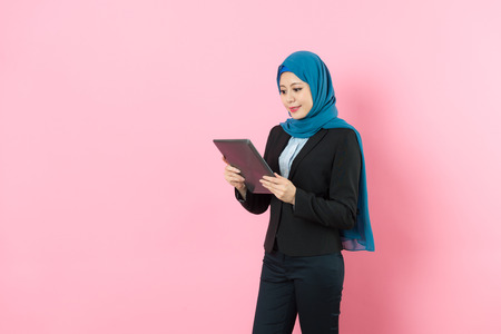 smiling pretty muslim female office worker using mobile digital tablet computer browsing working process isolated on pink background. Stock Photo