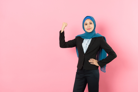 happy beautiful muslim woman worker wearing business suit and showing powerful muscle looking at camera isolated on pink wall background. Stock Photo