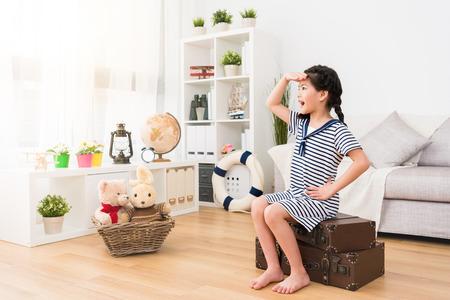 beleza jovem menina crianças sentado na mala retro, olhando a distância, quando ela se veste como marinheiro jogando jogo de viagem com brinquedos na sala de estar. Foto de archivo