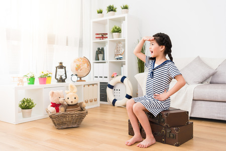 young beauty little girl children sitting on retro suitcase looking distance when she dress up as sailor playing travel game with toys in living room. Banco de Imagens