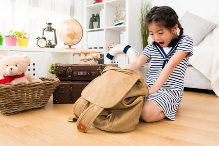 young cute little girl sailor opening personal adventure luggage backpack feeling surprised.