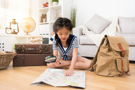 happy pretty little girl preparing personal luggage in backpack and sitting on floor using magnifier looking map ready going to adventure.