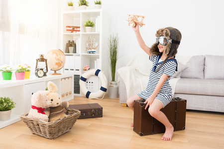happy pretty female kid pilot sitting on vintage suitcase and holding wooden airplane toy making fly status. Archivio Fotografico