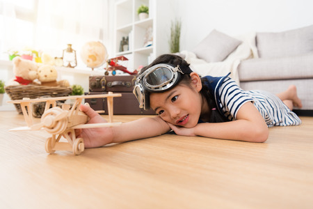 beautiful cute little girl lying down on floor resting when she playing aviator game with wooden airplane toy in living room. Stock Photo