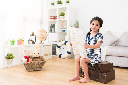 smiling pretty little female sailor holding travel map researching adventure plan and sitting on suitcase looking at camera.