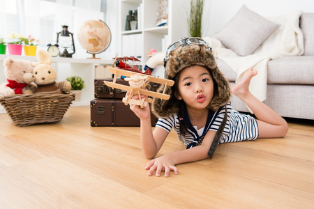 lovely pretty little girl dress up as aviator lying down on floor and playing vintage airplane and looking at camera making cute emoticon.