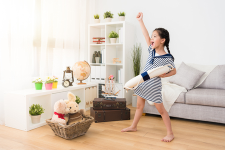 cheerful young little girl sailor carrying life buoy standing in playroom wooden floor and making posture preparing adventure.