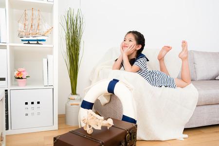 彼女はリビングルームで遊ぶとき、ソファのソファの空想と考える冒険旅行計画に横たわって美しいかわいい小さな女の子の女の子。